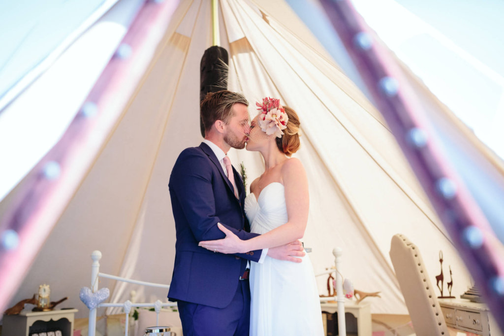 Bride and Groom kissing inside the bell tent