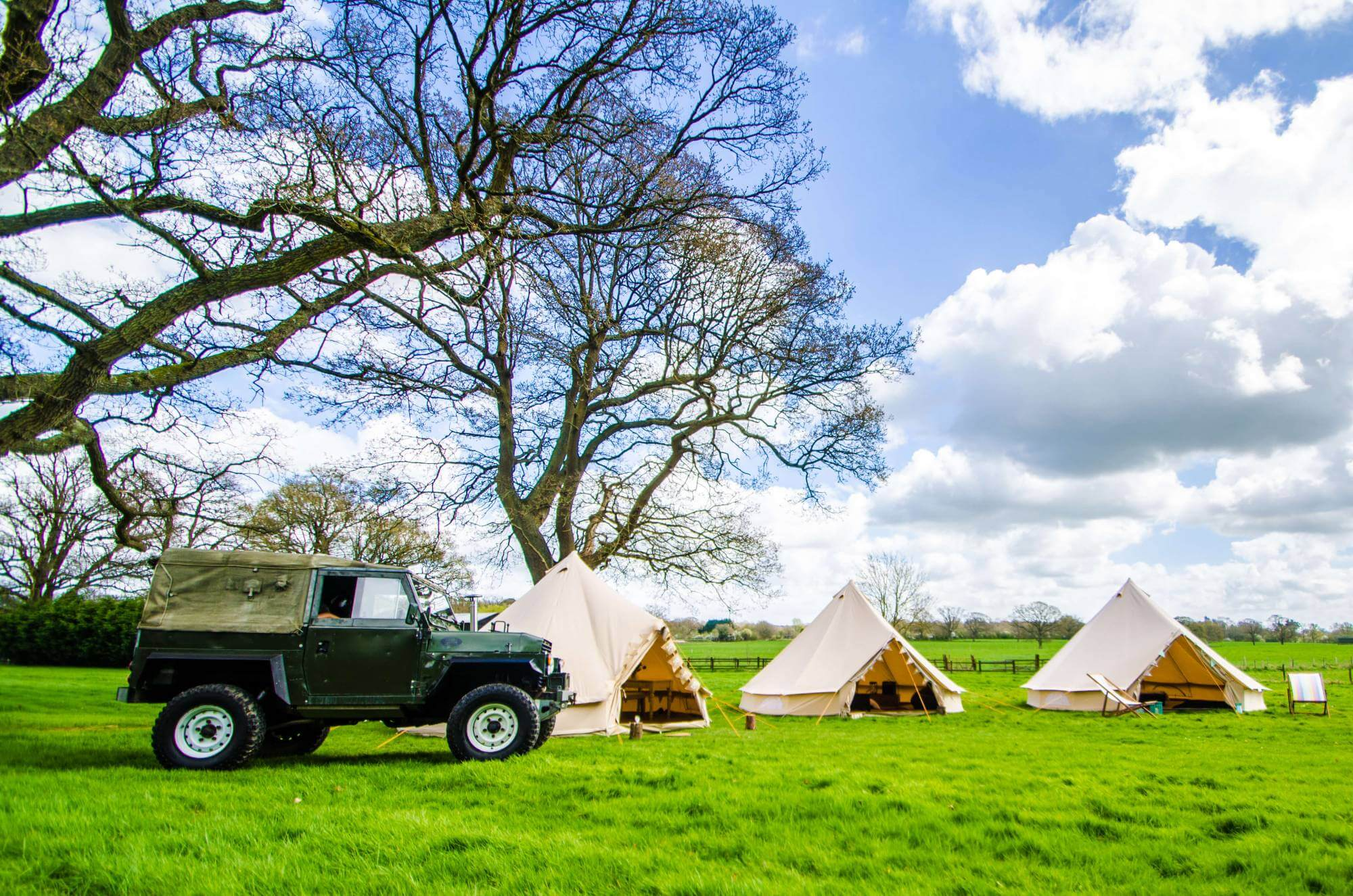 Land rover packed out side three Bell Tents