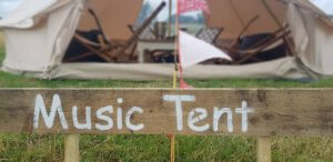 Music tent sign with a blurred image of a Bell Tent