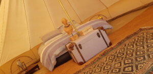 A bed and luggage inside a Bell Tent
